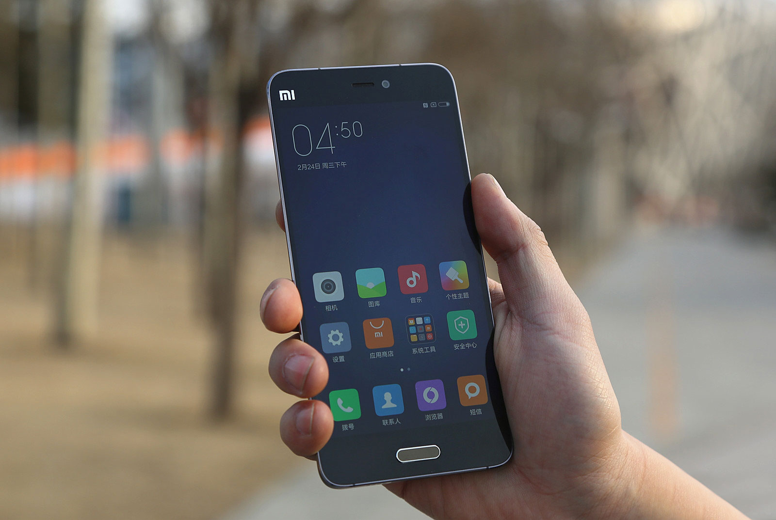 Xiaomi Mi 5 held in hand, checking out the display of the device