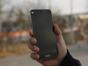 Holding in hand Xiaomi Mi 5 smartphone, checking out device front design