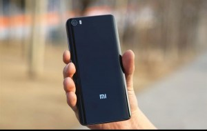 Holding in hand Xiaomi Mi 5 smartphone, checking out device back design
