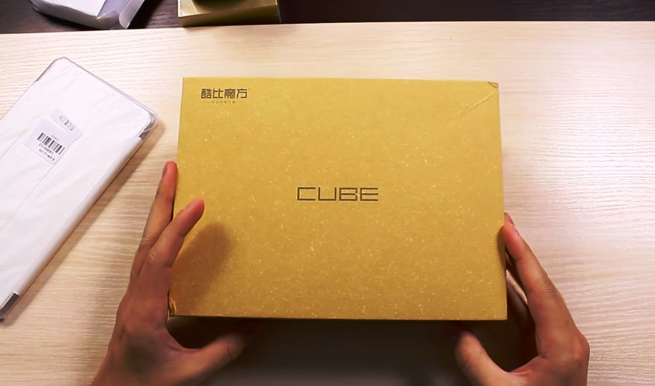 Cube T8 packaging, held by two hands on the table.