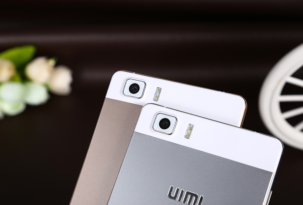 UIMI U5 Two phones, gold and silver color, camera hump pictured, white flower and wheel in the background.