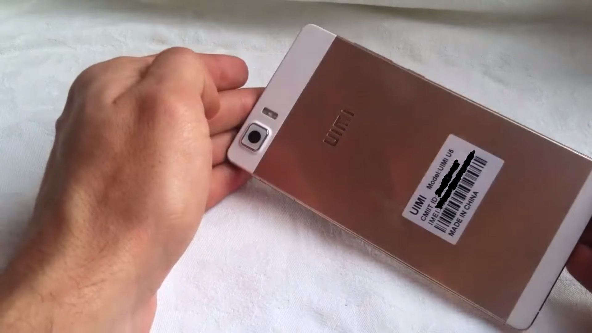 UIMI U5 Held in hands, golden color, back side view, white background.