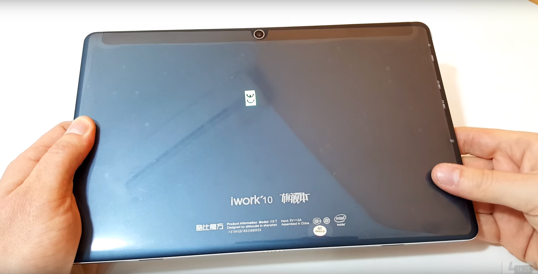 Cube iWork 10 tablet, held in hands, back side, white background.