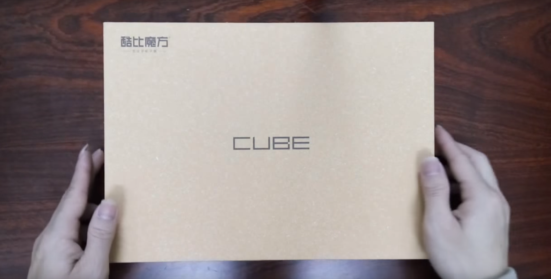 Cube iWork 10 packaging - brown box with the Cube logo on a dark brown table, held in hands.