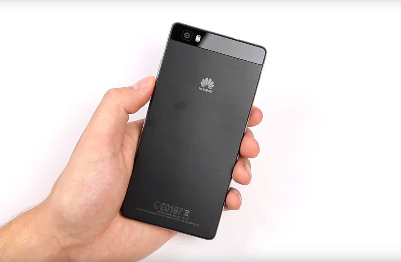 Huawei P8 Lite held in hand, black phone, white background