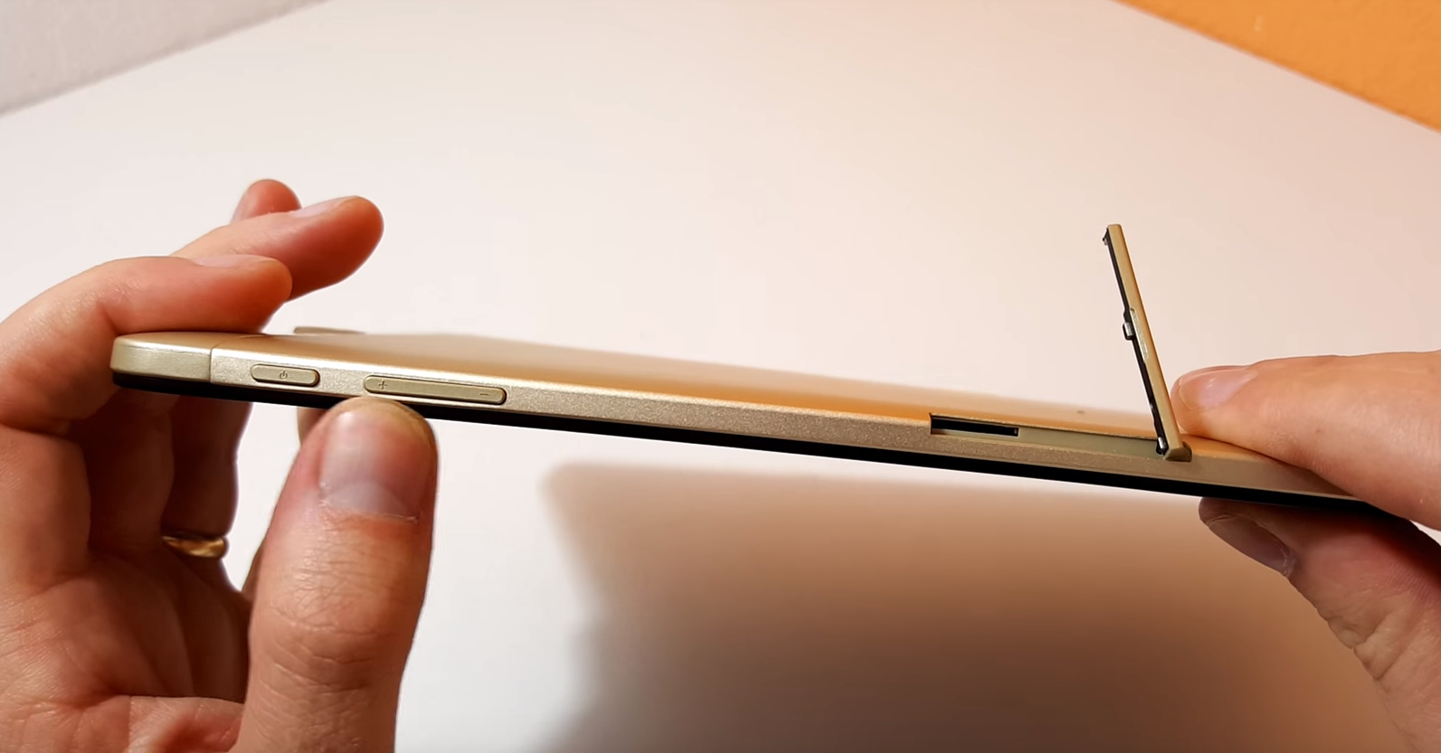 Onda V919 Air, held in hands, showing the right side of the tablet, white table in the background.