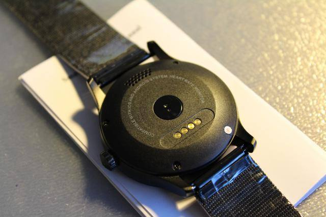 K88H smartwatch showing its back side while lying on a white paper located on a gray desk.