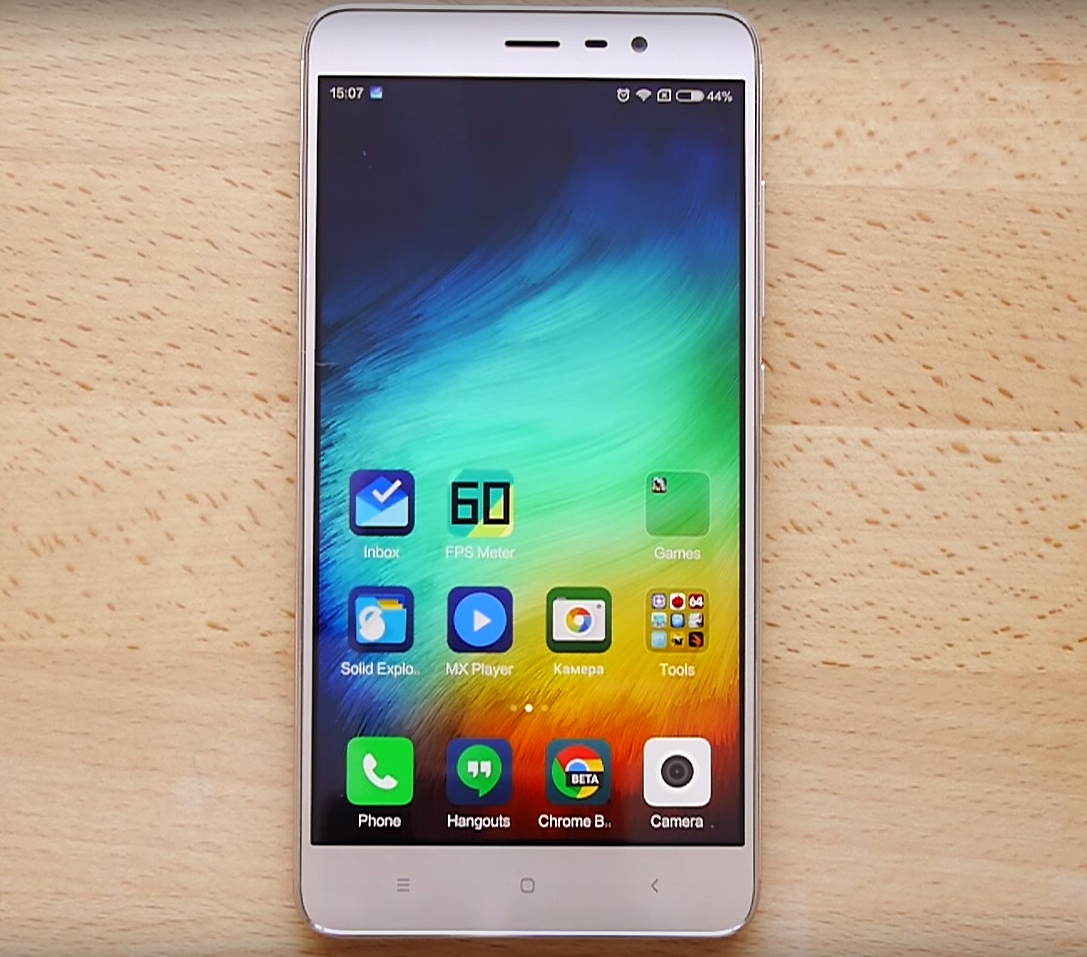 XiaoMi Redmi Note 3 Pro lying on the wooden table, showing MIUI 7 home