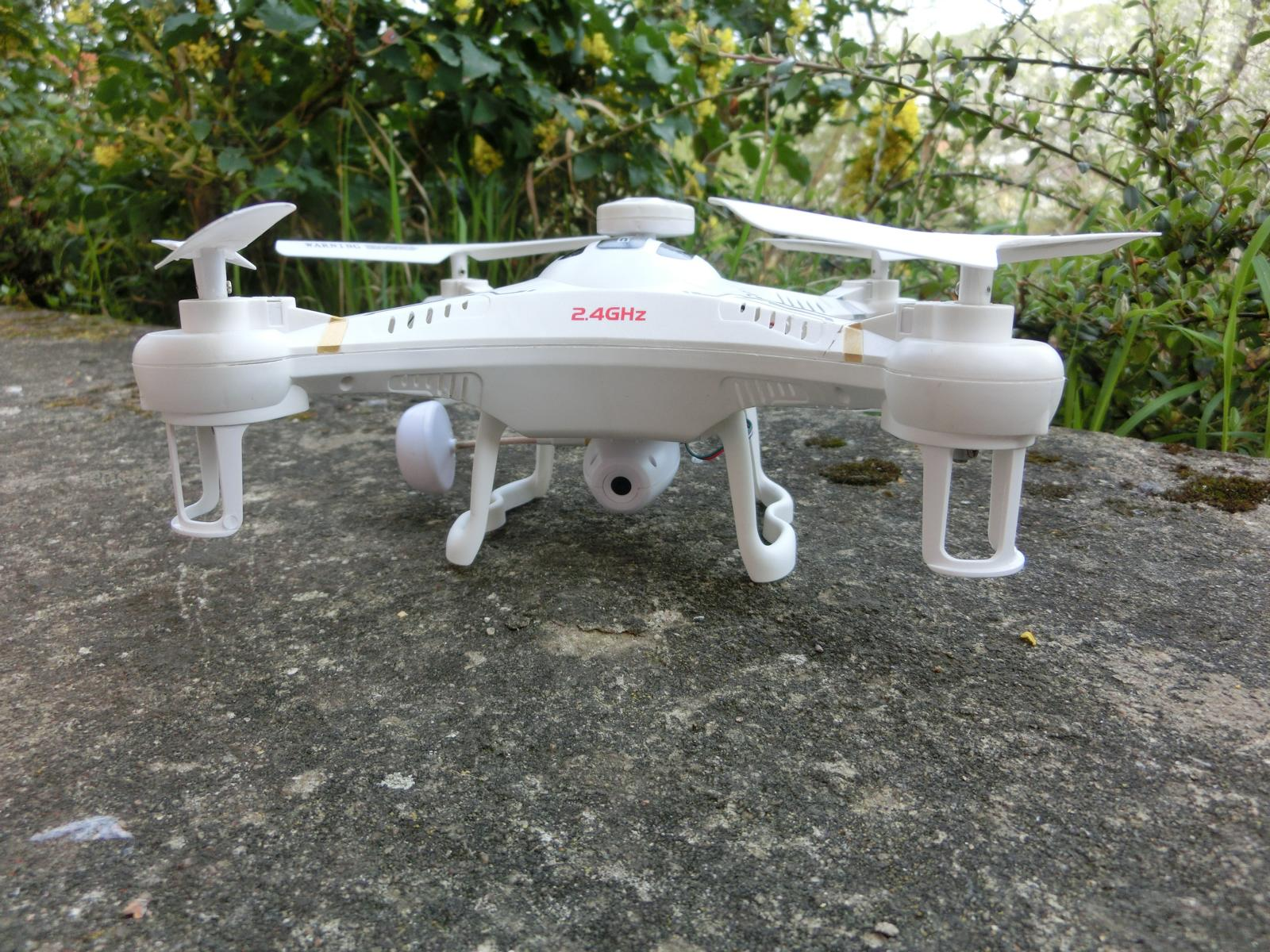 Xinlin X118 Quadcopter standing on the rock with plants in the background.