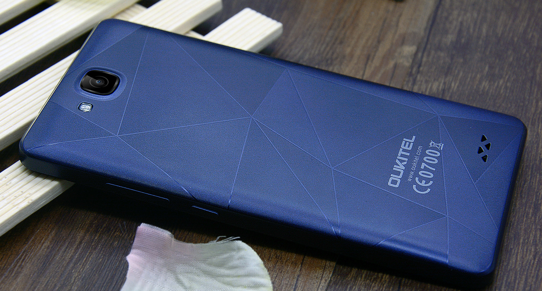 Oukitel C3; deep blue version shown from the back while lying on a wooden table.