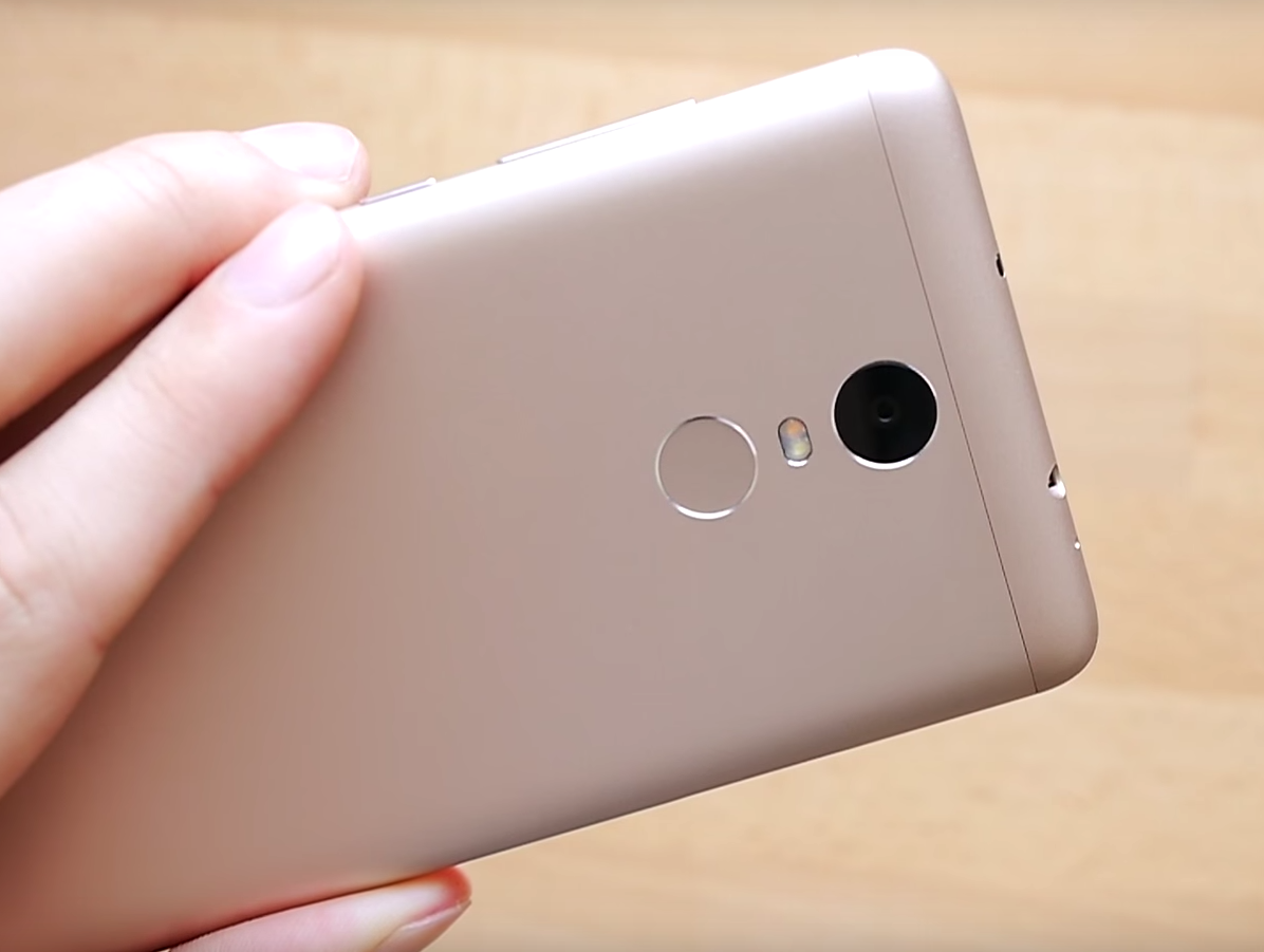 XiaoMi Redmi Note 3 Pro silver version held in hand, showing back and camera, wooden table in the background.