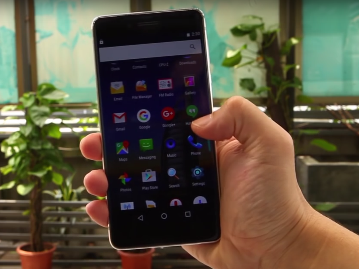 Ulefone Future held in the hand, display turned on, plants in the background