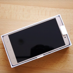XiaoMi Redmi Note 3 Pro in the opened white box lying on a wooden table.