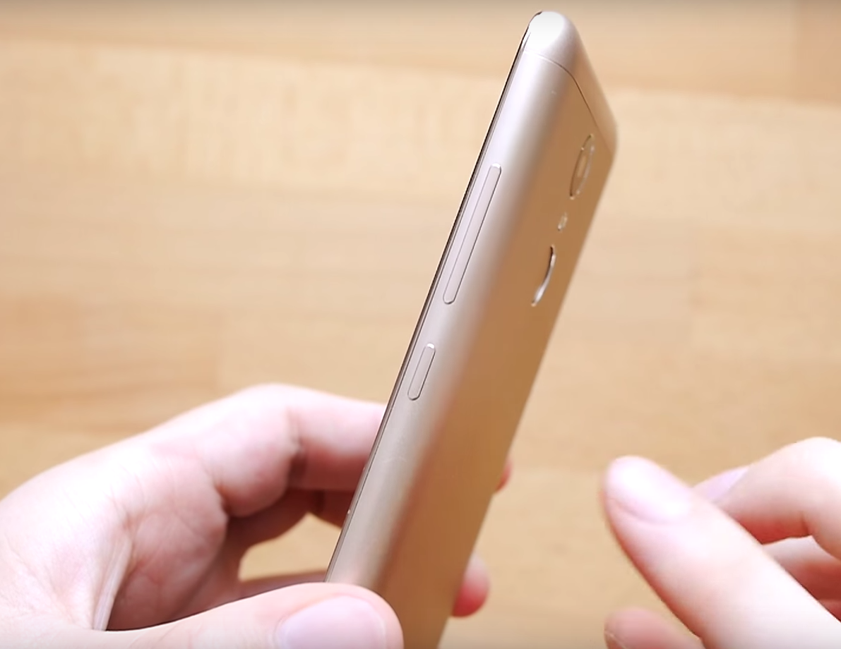 XiaoMi Redmi Note 3 Pro showing the right side of the silver phone, held in hand, wooden table in the background.