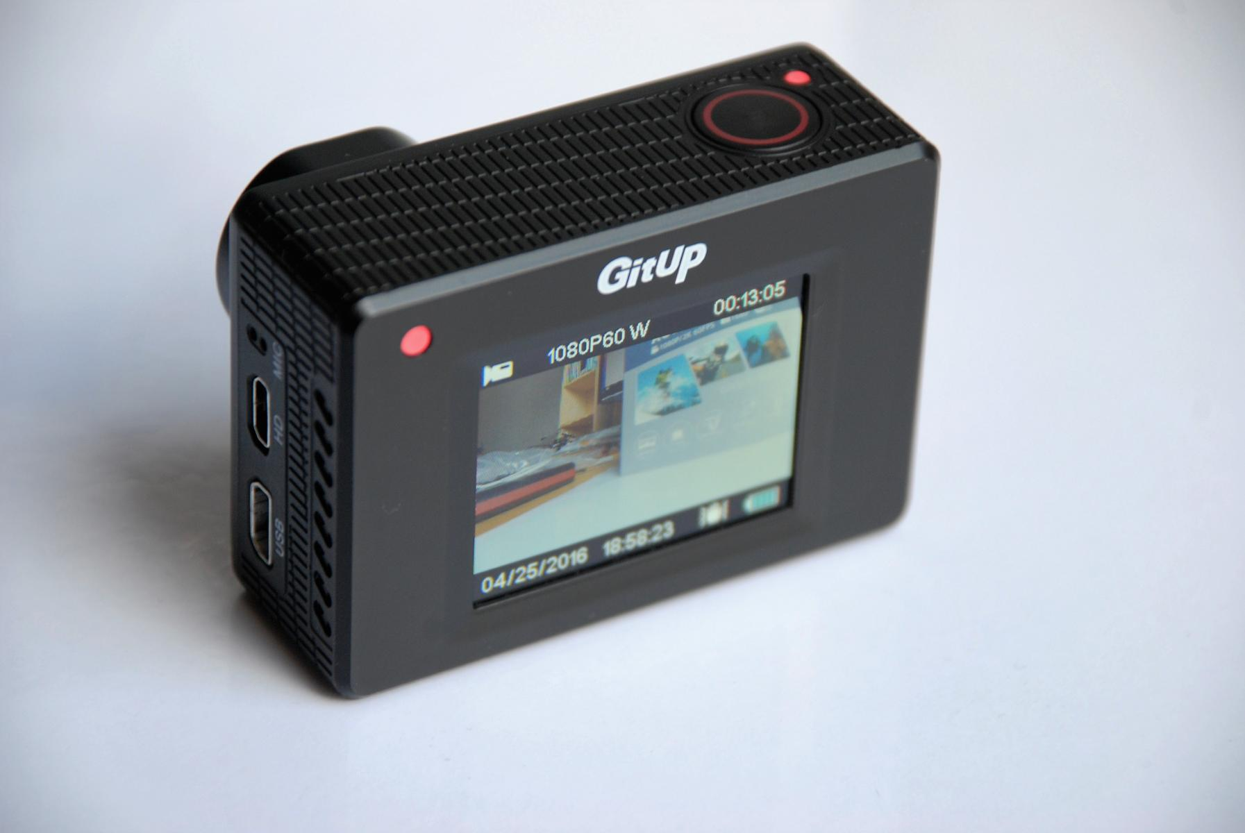 GitUp Git2 Pro Action Camera display turned on, siting on the white desk.