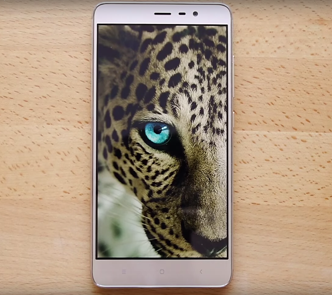 XiaoMi Redmi Note 3 Pro showing a leopard on a display, lying on the wooden desk.