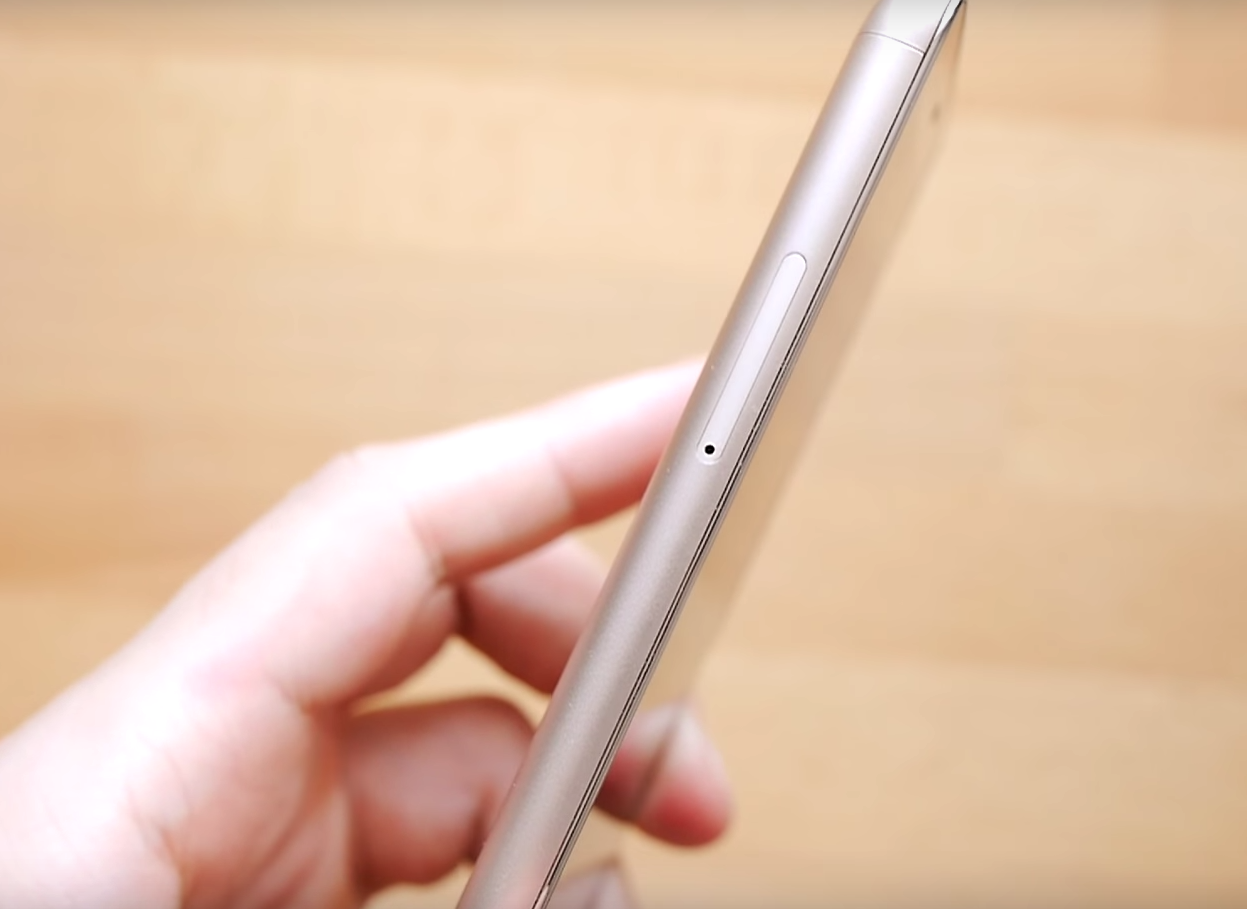 XiaoMi Redmi Note 3 Pro showing left side of the silver phone, held in hand, wooden table in the background.
