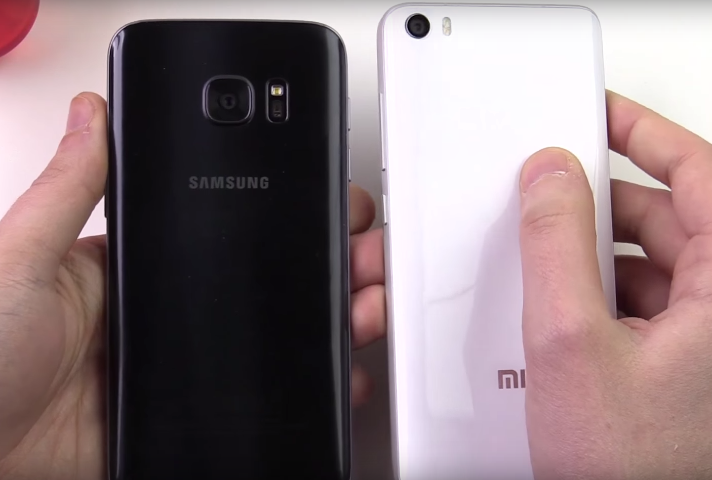 Xiaomi Mi 5 vs. Samsung Galaxy S7 holding the devices in hands, showing their back sides; white table in the back.